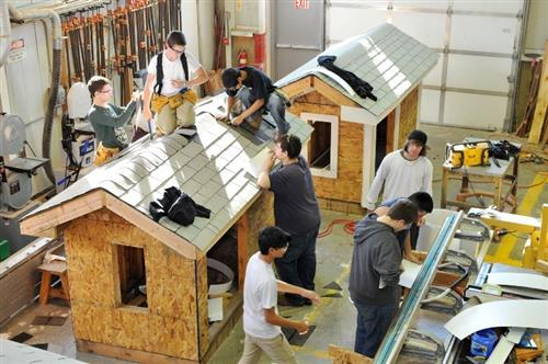 students working on house structures in shop