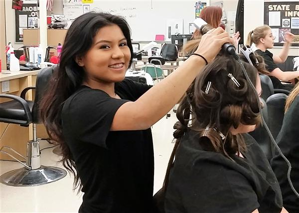 Cosmetology student curling hair