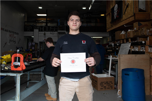 Photo of Devin Conahay holding student of the month certificate in plumbing shop