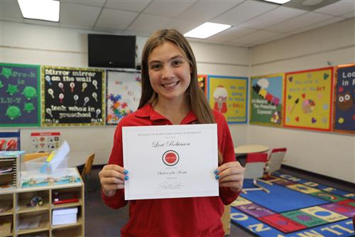 Photo of Lexi Robinson holding student of the month certificate in the preschool classroom